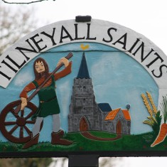 The village sign at Tilney All Saints depicts Tom with whell and axle.